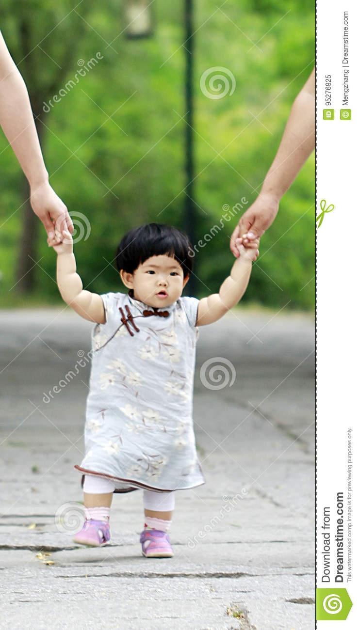 Lovely Chinese Ba Girl In Cheongsam Learn To Walk Stock Image